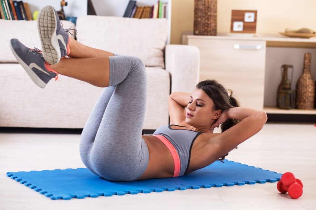 Attractive female doing exercise at home.